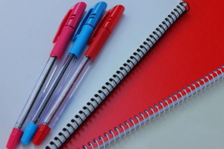 Red notebook and pen photo