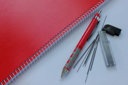 Red notebook and Mechanical pencil with pencil lead photo
