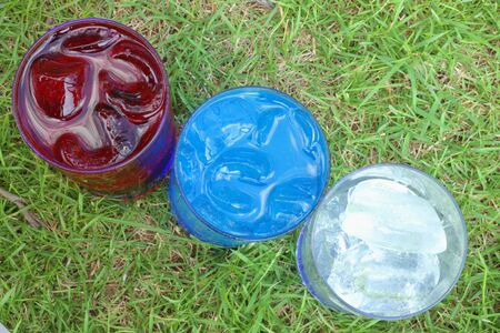 Blue, red soda water with ice in a glass on a green grass  photo