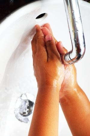Washing hands in a sink.