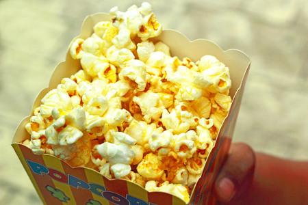 Child holding popcorn a caramel coated