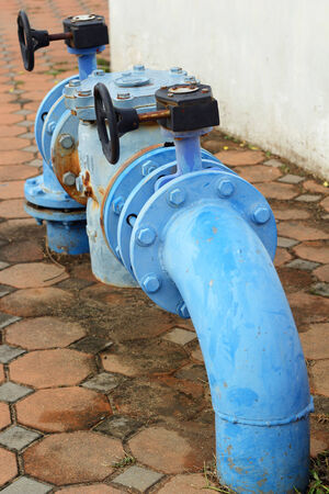 junction pipe: blue rusty metal industrial water pipes with a valve.