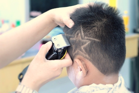 hair clippers: The boys haircut with clipper and razor in the barber shop Stock Photo