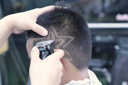 scissor cut: The boys haircut with clipper and razor in the barber shop Stock Photo
