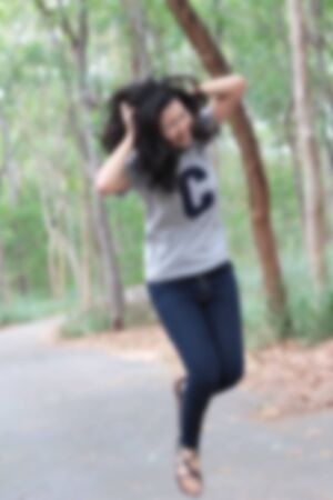 cheerfully: Blurred woman cheerfully at the park