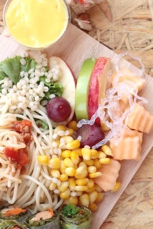 Pasta spaghetti with salad mix fruit.
