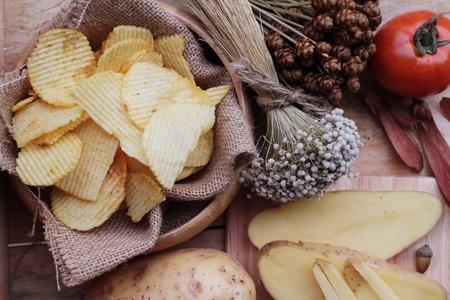 comida chatarra: Patata frita y patatas frescas en el fondo de madera