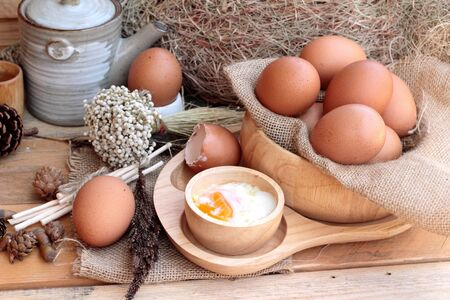 eggcup: soft-boiled egg and eggs on wood background Stock Photo