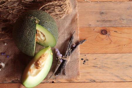 globose fruits: Green cantaloupe melon fruit juicy on wood background Stock Photo