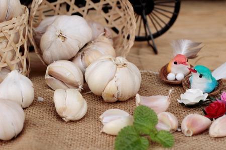 clove plant: Raw garlic has health benefits on wood background Stock Photo