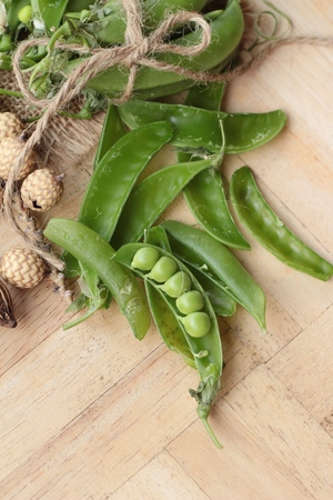 peas in a pod: Fresh green peas pod on wood background