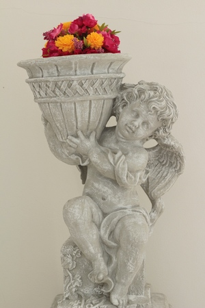 Statue of cupid in garden with flower