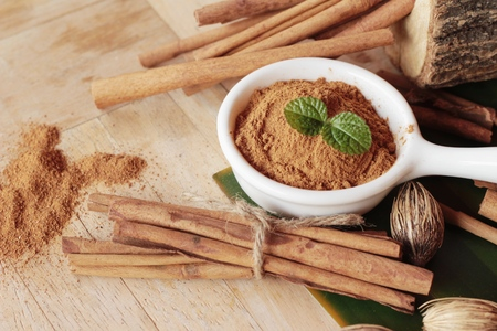cinnamon powder and sticks on wood background