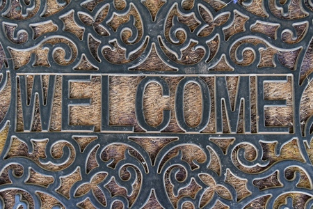 front house: Welcome door mat on background and texture