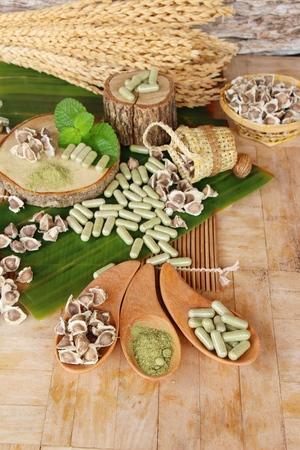 Moringa capsule for health on wood background Stock Photo