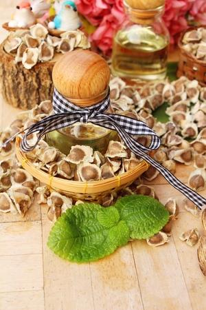 Moringa oleifera oil and seeds on wood background Stock Photo