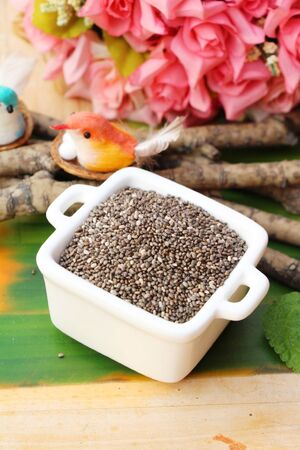 Organic chia in seeds on wood background