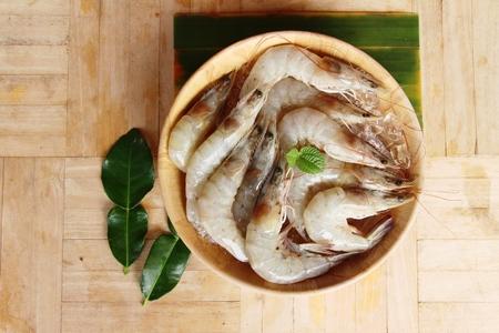 Fresh shrimp for cooking on wood background