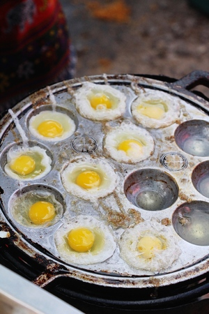 Grilled quail eggs in a pan pits Фото со стока