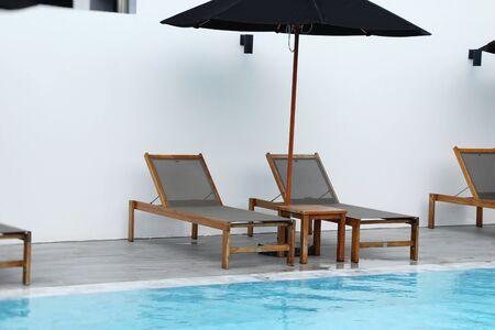 Cozy daybed with umbrellas by the pool Banco de Imagens
