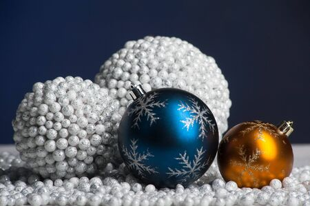 Blue and yellow christmas decoration on artificial snow on blue background photo