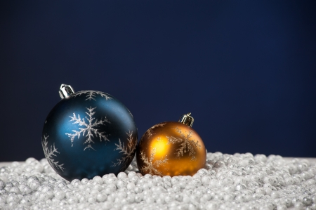 Christmas tree decoration toys lying on artificial snow on blue background with copyspace photo