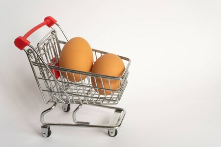 toy little consumer food trolley from steel with red plastic handle on a gray background with two fresh eggs inside. empty space 版權商用圖片