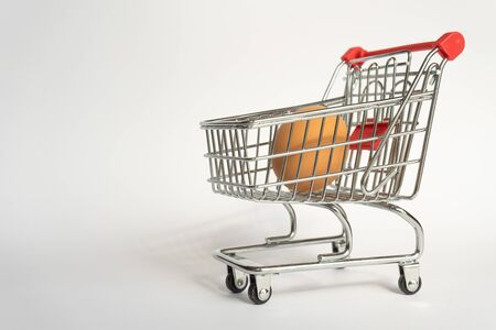 toy little consumer food trolley from steel with red plastic handle on a gray background with one fresh egg inside. empty space, right position