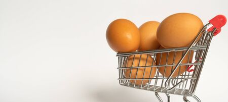 Banner. toy little consumer food trolley from steel with red plastic handle on a gray background with five fresh egg inside. empty space 版權商用圖片