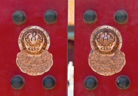Ancient china lion knockers on the red temple door photo