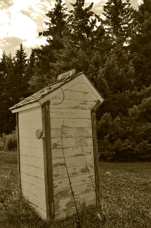 Sepia toned image of an old Outhouse.