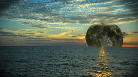 A composite of the moon setting in the sea with clouds    Stock Photo