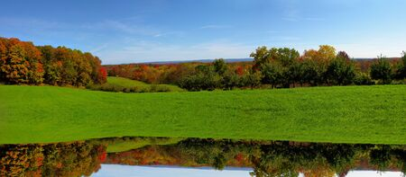 A fall scenic panoramic shot of a Lake with a reflection in the water              Stock Photo