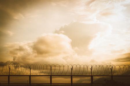 prisoner of war: barbed wire fence at sunset