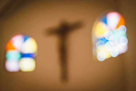 cross and stained glass window in the church blur abstract background
