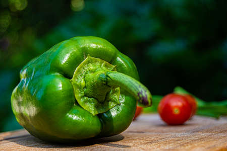 green bell pepper on wood with tomatoes background