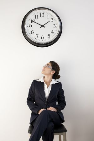 vertically: Young female office worker watching clock. Vertically framed shot.