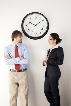 Male and female businesspersons under clock. Vertically framed shot. photo