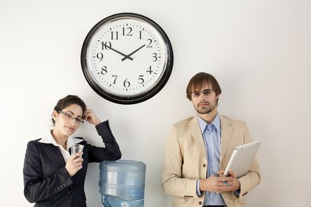 businesspersons: Male and female businesspersons talking under clock. Horizontally framed shot.