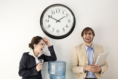 water cooler: Male and female businesspersons talking under clock. Horizontally framed shot.