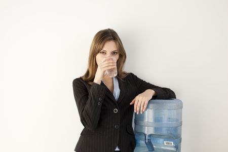 Female office worker getting a drink at water cooler. Horizontally framed shot. photo