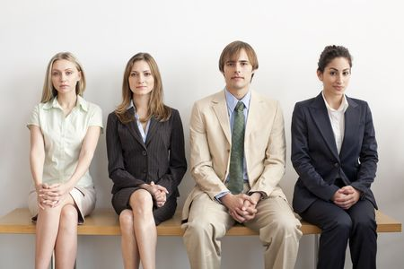businesspersons: Four businesspersons sitting on bench. Horizontally framed shot. Stock Photo