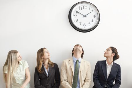 clock: Four businesspersons sitting on bench looking up at clock. Horizontally framed shot.