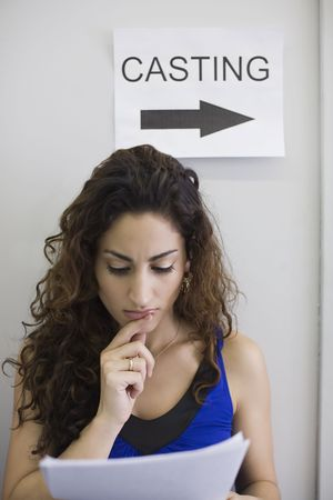 Young female studying a script under a sign saying casting. Vertically framed shot.