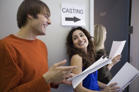 horizontally: Three people in line at casting call. Horizontally framed shot. Stock Photo