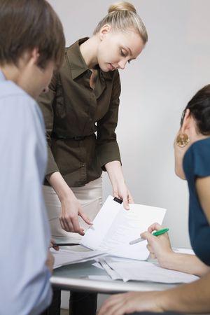 businesspersons: Businesspersons discussing paperwork. Vertically framed shot.