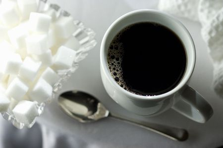 Black coffee in white cup with sugar cubes and spoon on white table cloth photo