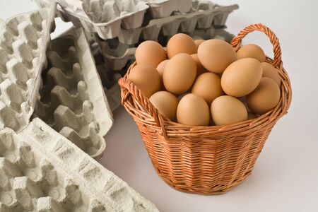 Basket full of brown eggs with empty egg cartons photo