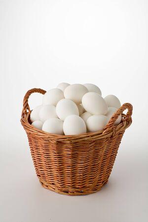 Witte eieren in rieten mand geïsoleerd