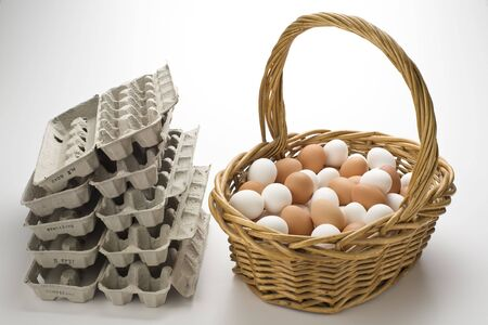 Basket filled with brown and white eggs with empty  egg cartons Imagens